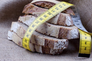 Dieting concept. Tape measure wrapped around slices of bread